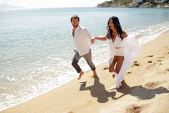 Two happy just married young adults, men holding his wife, running in the water, isolated on a seascape background. royalty free stock images