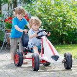 Two happy kid boys having fun with toy car Royalty Free Stock Photos