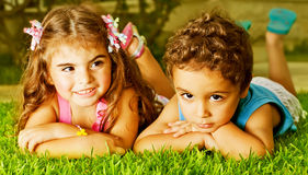 Two happy kids. Picture of two happy kids laying down on fresh green grass, brother and sister enjoying summer holiday, cute girl and pretty boy having fun stock photos