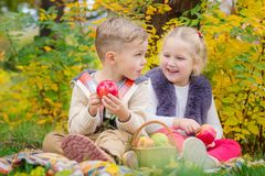 Two happy kids in an autumn park at a picnic. Eating apples Royalty Free Stock Photography
