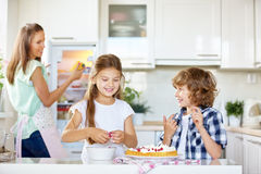 Two happy kids baking cake with red currants Royalty Free Stock Photo