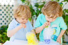 Two happy kids boys making experiment with colorful bubbles. Two little boys making experiment with colorful soap bubbles and water, outdoors. Kids, best friends stock image