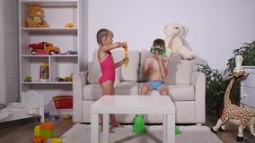 Two happy kids in diving mask sitting together in sofa.  stock video footage
