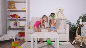 Two happy kids in diving mask sitting together in sofa.  stock footage