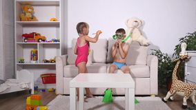 Two happy kids in diving mask sitting together in sofa stock footage