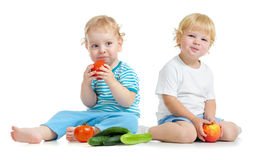 Two happy kids eating healthy food fruits and vegetables Stock Photo
