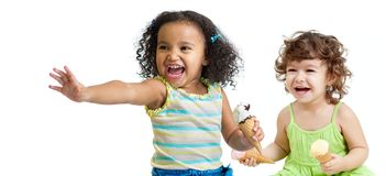 Two happy kids eating ice cream on white. Two happy kids eating ice cream isolated on white royalty free stock images