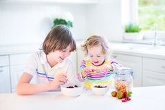 Two happy kids having fruit for breakfast drinking juice Royalty Free Stock Photos