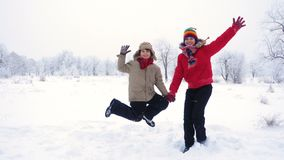 Two kids jumping together on winter landscape. Two happy kids jumping together on winter snow landscape, slow motion 250 fps stock footage