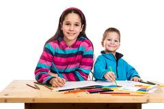 Two happy kids learn to draw together. Isolated on white Stock Photos