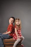 Two Happy Kids Looking at Eachother. A brother and sister sibling are sitting on a crate. The children are looking at each other for a friend or love concept Stock Photos