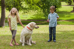 Two happy kids with pet dog at park Stock Photography