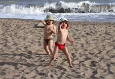 Two happy kids playing on beach Stock Photos