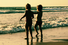Two happy kids playing on the beach stock images
