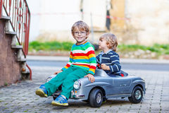 Two happy kids playing with big old toy car in summer garden, ou Royalty Free Stock Image