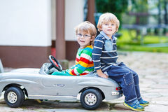 Two happy kids playing with big old toy car in summer garden, outdoors royalty free stock photography
