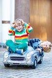 Two happy kids playing with big old toy car in summer garden, ou Stock Image