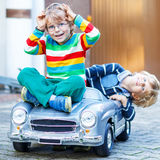 Two happy kids playing with big old toy car in summer garden, ou Stock Photos