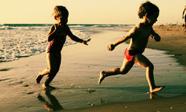 Two Happy Kids Playing On The Beach