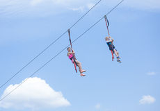 Two happy kids playing on a zip line view from below. Two happy kids enjoying a fun ride on a zip line high above the ground. View from below with simple blue royalty free stock images
