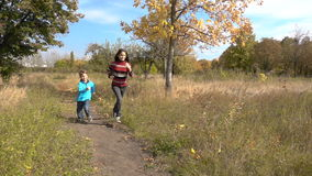 Two kids running together on autumn park. Two happy kids running together on sunny autumn park stock video footage