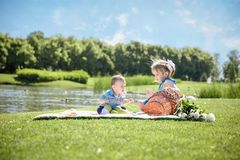 Two happy kids sitting on picnic in the park stock photo