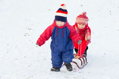 Two happy kids with sled walking on snow slope. In winter clothes Royalty Free Stock Photo