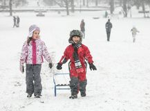 Two Happy Kids Snow Sled. Two happy kids are pulling a sled in the snow during a cold winter day stock photos