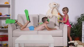 Two happy kids in swimsuits. Boy in diving mask Float on the couch and The girl is blowing bubbles in room stock video footage