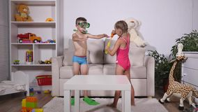 Two happy kids in swimsuits. Boy in diving mask and The girl is blowing bubbles in room stock footage