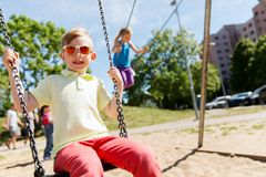 Two happy kids swinging on swing at playground Stock Photo