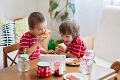 Two happy kids, two brothers, having healthy breakfast sitting a