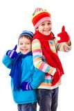 Two happy kids in winter clothes with thumbs up sign royalty free stock image