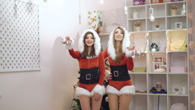 Two happy ladies dancing, smiling with Christmas toys in 4K.  stock video footage