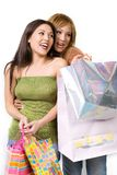 Two happy ladies shopping. Two happy, cute and young ladies with shopping bags. White background Royalty Free Stock Photography