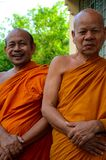Two happy laughing Buddhist monks in robes Hat Yai Thailand. Hat Yai, Thailand - August 28, 2015: Two senior Buddhist monks laugh and smile for the camera. The royalty free stock images