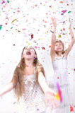 Two happy laughing girls. Two happy excited laughing girls under sparkling confetti shower Royalty Free Stock Images
