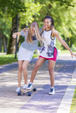 Two Happy Laughing Teenager Girls Skating Longboard Together in Park Stock Photos