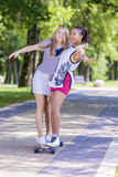 Two Happy Laughing Teenager Girls Skating Longboard Together in Park. Stock Image