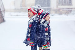 Two happy little boys having fun with snow in Stock Photo