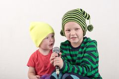 Two Happy little boys in smart clothes sing a song with a microphone at home. Preparing for the Christmas Karaoke.  stock image