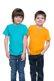 Two happy little boys. Are standing against the white background Royalty Free Stock Image