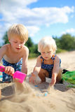 Two Happy little Children Playing in the Sand at the Beach. Two happy little children, a boy and his baby sister, are playing in the sand at the beach, building Stock Images