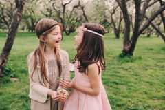 Two happy little girlfriends picking flowers in spring garden. Sisters spending time together outdoor. Royalty Free Stock Photography