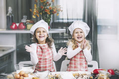 Two happy little girls child cook with flour and dough at the ta Stock Photography
