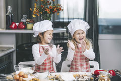 Two happy little girls child cook with flour and dough at the ta Royalty Free Stock Photography