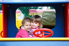 Two happy little girls embracing together. Two happy Caucasians little girls embracing together on playground Royalty Free Stock Images