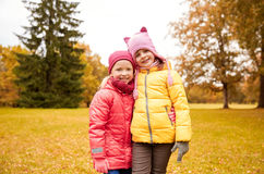 Two happy little girls hugging in autumn park Stock Photo