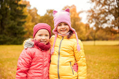 Two happy little girls hugging in autumn park Stock Photos
