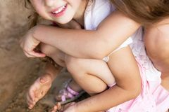 Two Happy little girls laughing and embracing at the summer par. Two Happy little girls laughing and embracing at the sunny park stock images